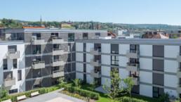 Blick vom Innenhof auf einen Wohnblock klimaneutral Leben im Stadtquartier, im Hintergrund Esslingen