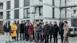 Group photo in front of an apartment block