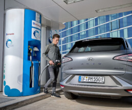 Young man refuels hydrogen vehicle Hyundai Nexo
