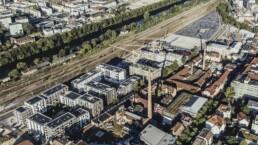Die Neue Weststadt - klimaneutrales Stadtquartier aus der Vogelperspektive. Im Hintergrund Bahnschienen und der Fluss Neckar.