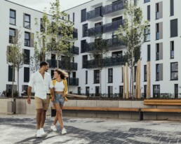 Young couple walk in the inner yard of an apartment block in the Neue Weststadt